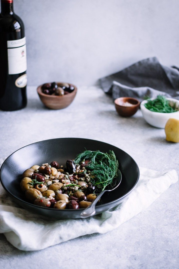 A black bowl with mixed olives and herbs with a bottle of wine and small bowls in the background.