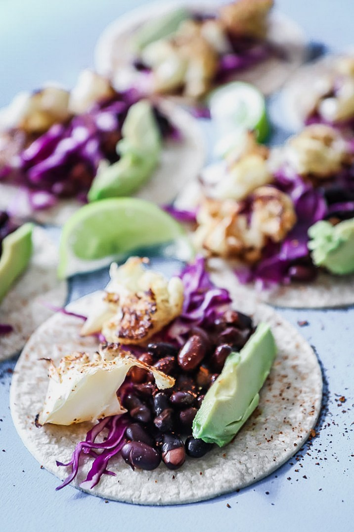 Chli lime cauliflower tacos on a blue table.