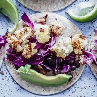 A vegan taco with cauliflower, chili, cabbage, and lime on a blue table.
