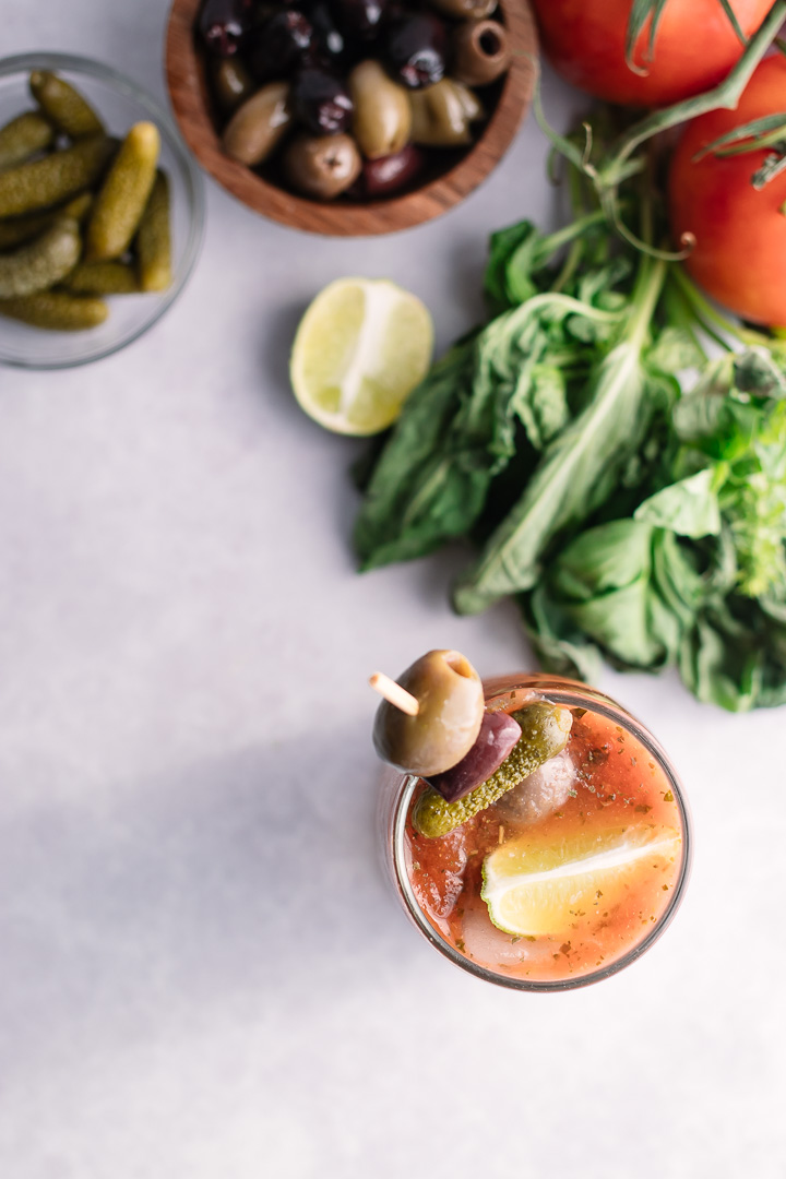 A flatlay photo of a bloody mary with olives and lime on a table with herbs and tomatoes.