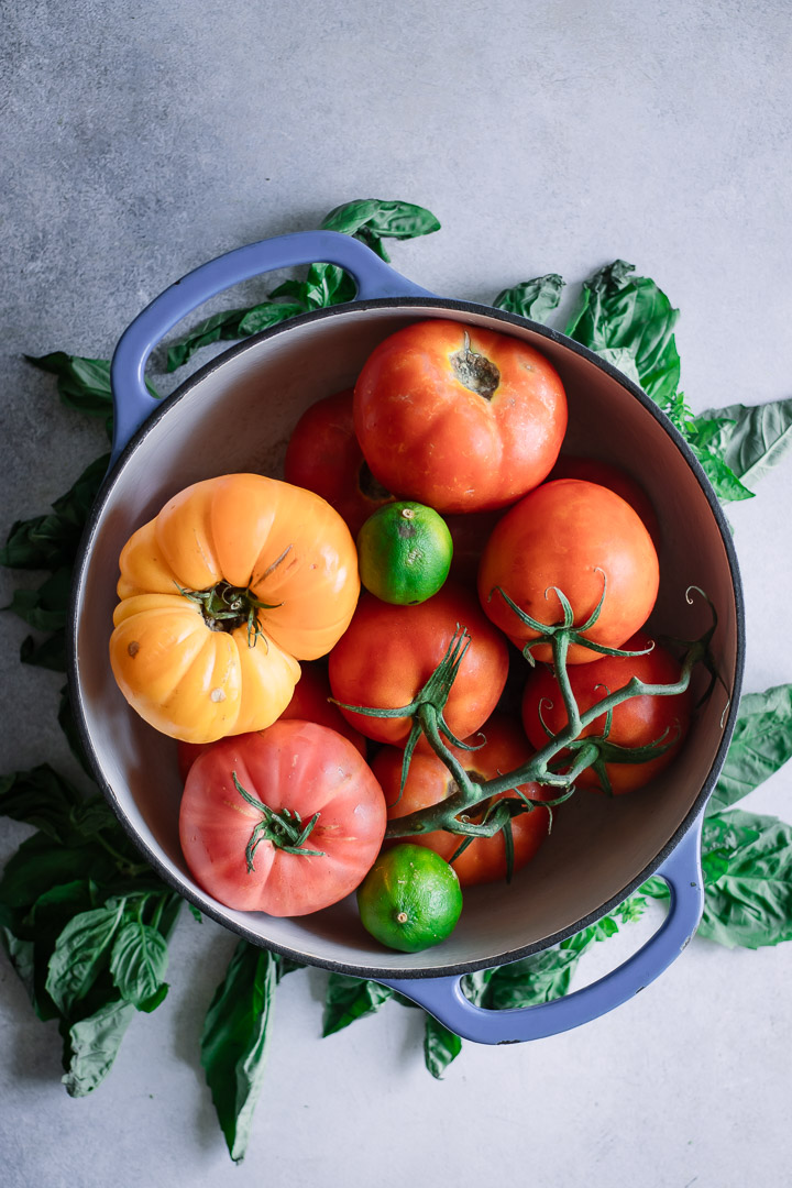 A soup pot filled with yellow and red tomatoes.