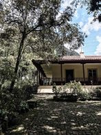 Simon Bolivar's house in Bogota. A white house on a hill with trees.