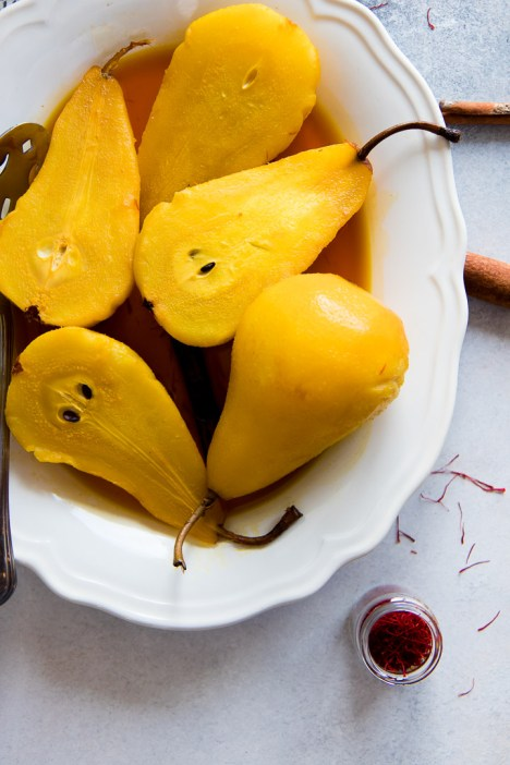 Saffron Poached Pears, a simple and seasonal fall and winter baked fruit dessert with saffron, apple cider vinegar, cinnamon, and brown sugar.