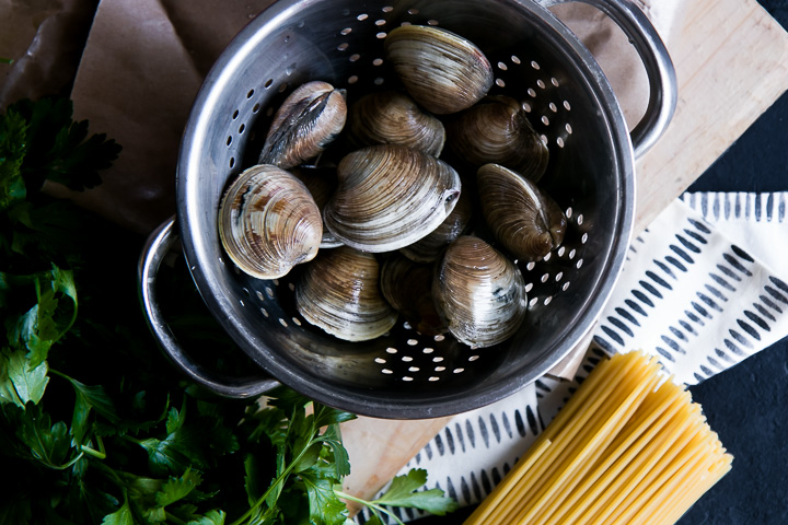 Clams in a silver metal strainer on a table next to parsley and bucatini pasta.