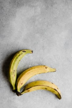 three plantains on a grey blue table for healthy baked patacones