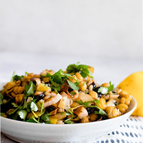 za'atar crispy chickpea and leek salad in a white bowl on a blue table with a white napkin and a side of lemon