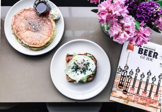 Pancakes and toast on a table with a magazine and a bouquet of flowers in Portland, Oregon.