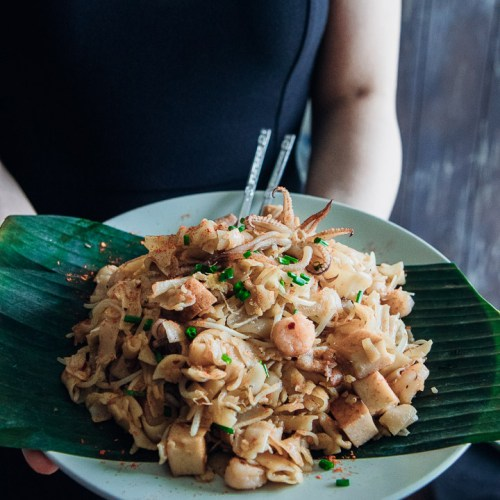 A woman holding a plate of Char Kuey Teow, a popular dish in Malaysian food culture.