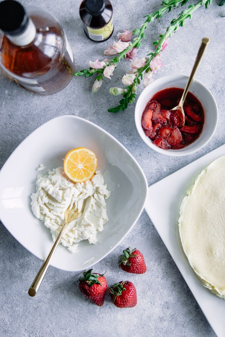 A crepe with ricotta and vanilla bourbon strawberries on a white plate on a blue table with flowers.