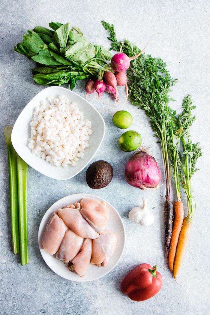 Chicken, hominy, celery, avocado, onion, garlic, limes, radishes and carrots on a table to make pozole verde.
