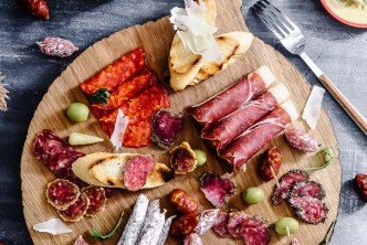 A round cheese and charcuterie board with Spanish finger foods on a blue table.