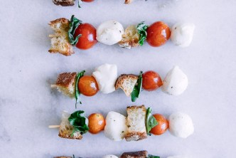 Skewers with cherry tomatoes, mozzarella, basil, and bread crumbs on a stick on a white table.