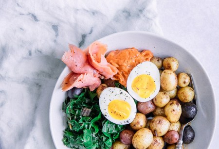 A breakfast bowl with salmon, potatoes, eggs, and chard in a white bowl on a white table with a cup of espresso.