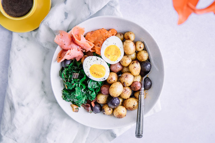 A savory breakfast bowl with salmon, eggs, and potatoes on a white bowl.
