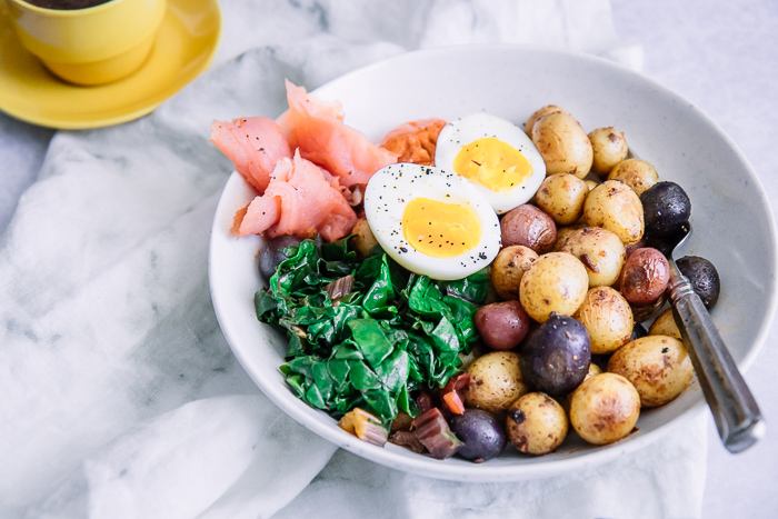 a breakfast for dinner bowl with salmon, eggs, and potatoes on a white table.