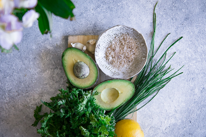 Avocados, salt, lemon, and fresh herbs on a cutting board.