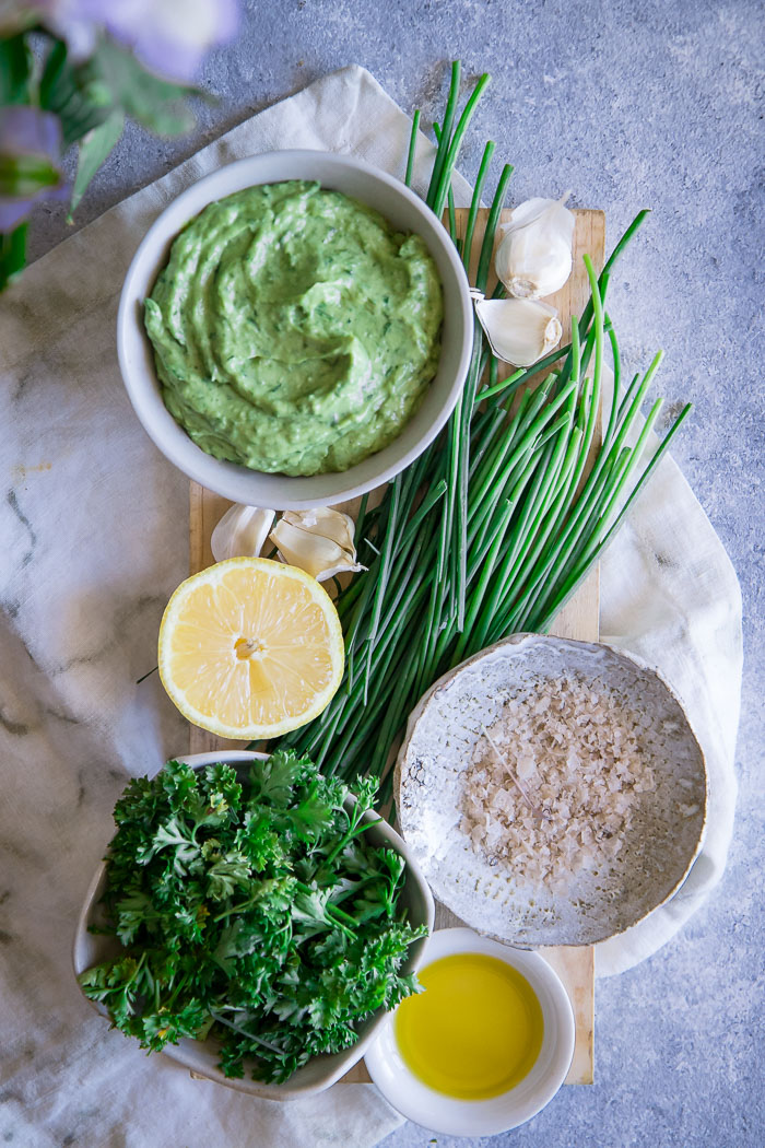 Green goddess dip on a cutting board with lemon, parsley, chives, and salt.