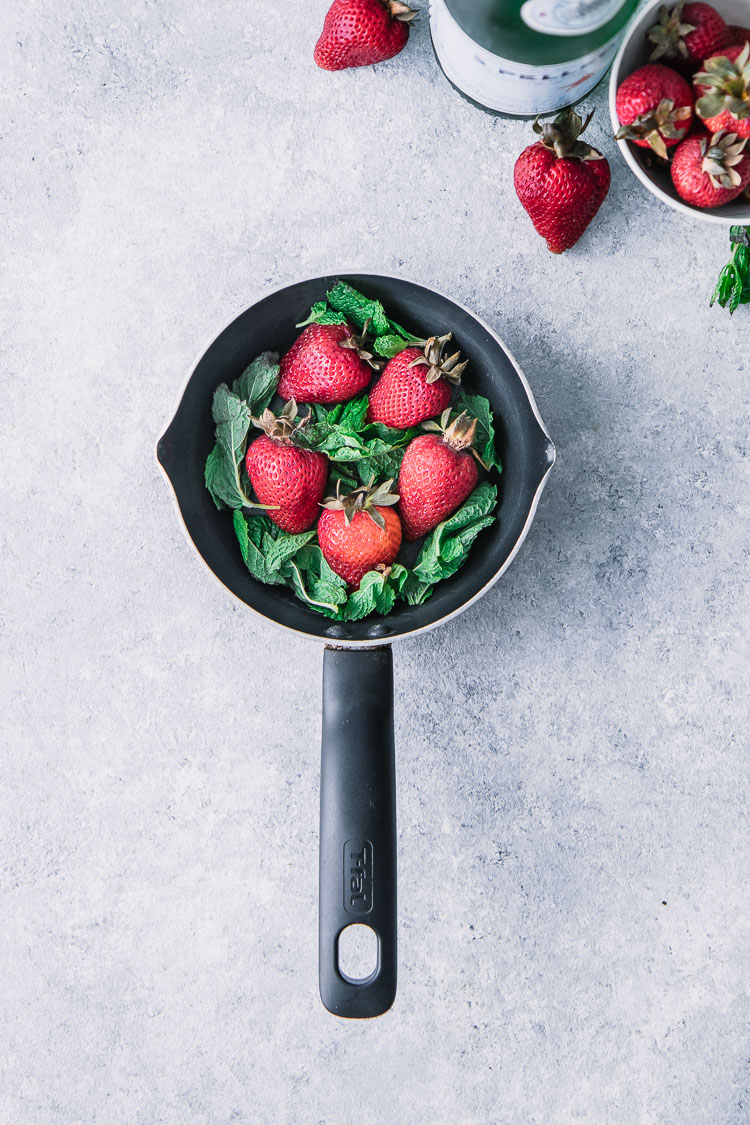 A small black saucepan filled with strawberries and mint.
