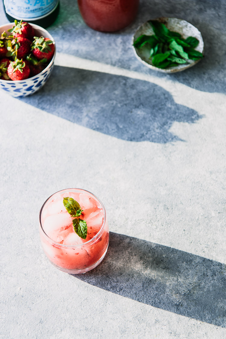 A pink sparkling water with strawberries and mint on a blue table.