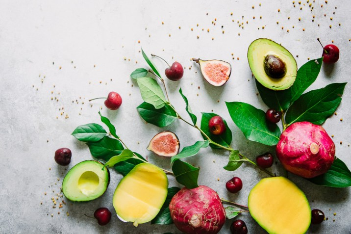 Mangos, cherries, avocados, beets, and figs on a white table with sprinkled bee pollen.