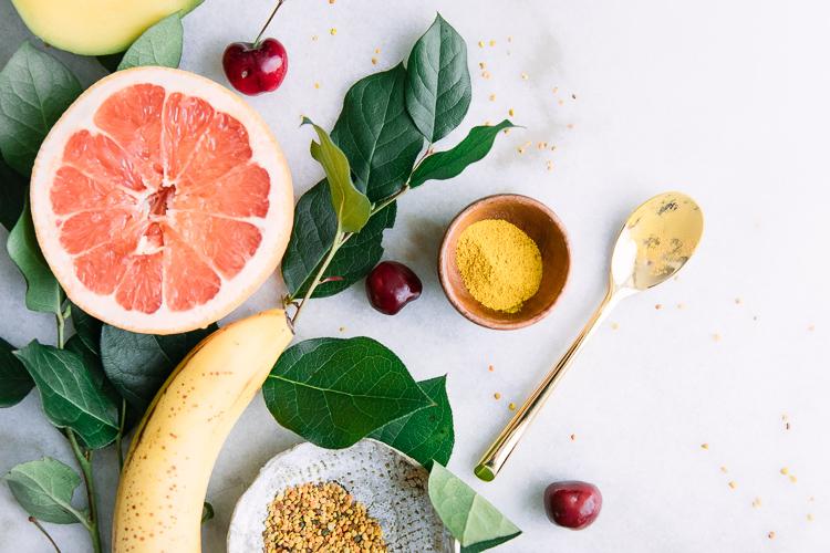 An arrangement of yellow superfoods including banana, grapefruit, bee pollen, mangos, and turmeric.