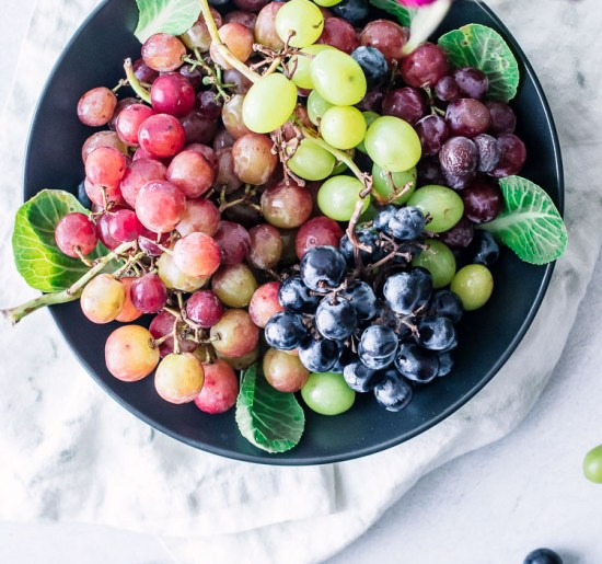 A black bowl of mixed green, red, and white grapes.
