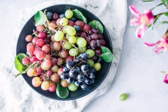 A bowl of assorted colorful grapes with a white napkin and flowers.