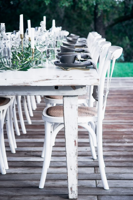A white table and chairs with a table styled for a late summer outdoor dinner.