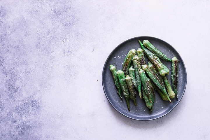 Okra on a plate on a white and blue table.