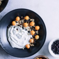 A bowl of yogurt with gooseberries and black currants.