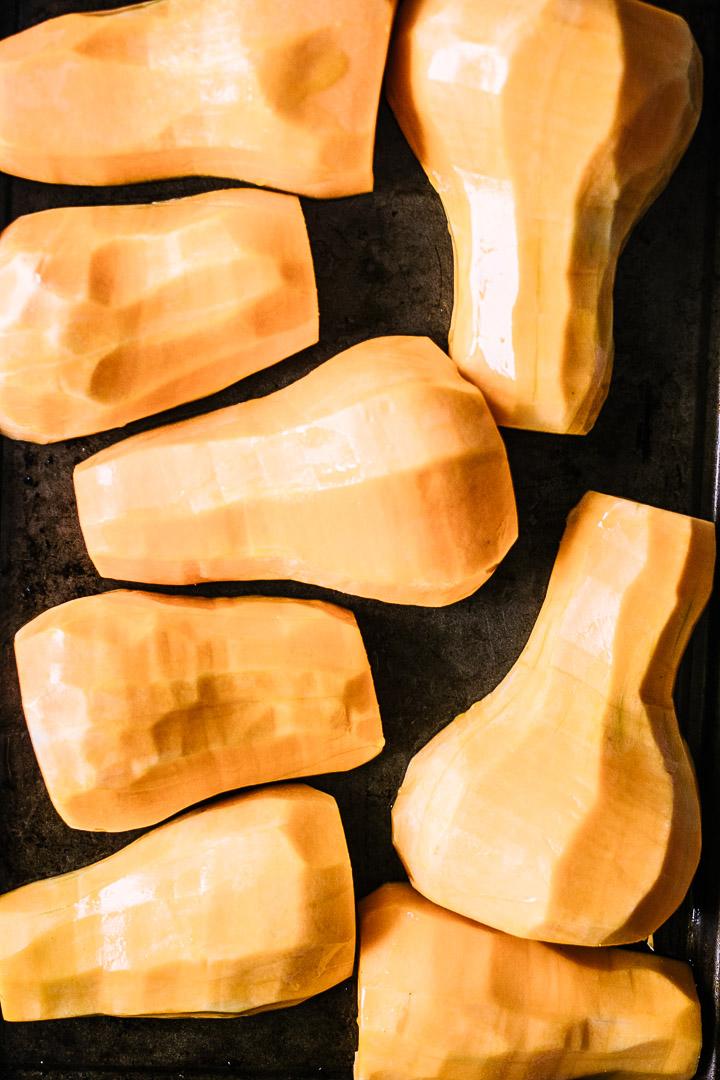 peeled butternut squash on a baking sheet