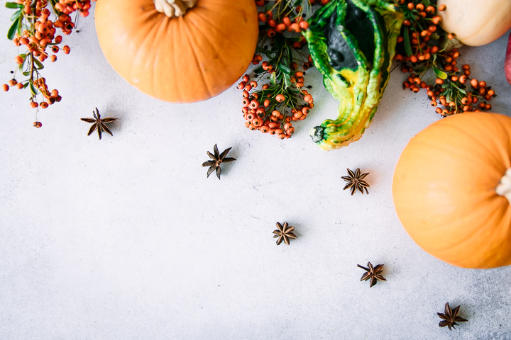 pumpkins, squash, and fall fruit and spices on a white table