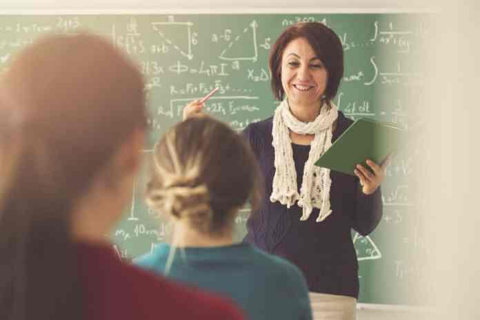 insegnante donna che spiega la lezione ai suoi alunni in classe