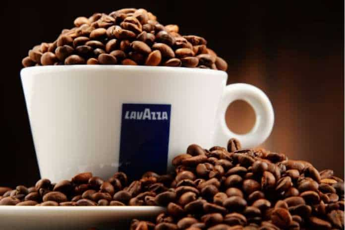 Tazzina del caffè Lavazza con chicchi di caffè