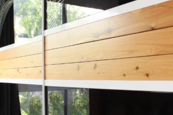 Black Sliding Glass Bedroom Doors with Cypress Pine Feature Panel