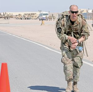 CAMP BUEHRING, Kuwait — Sgt. Dennis Albaugh of 64th Brigade Support Battalion, 3rd Armored Brigade Combat Team, 4th Infantry Division, crosses the finish line of the Bataan Memorial Death March marathon on Camp Buehring March 10, 2019. Albaugh finished the 26.2-mile event in 5 hours and 56 minutes. (Photo by Sgt. Liane Hatch)