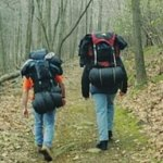 2 people walking with survival gear