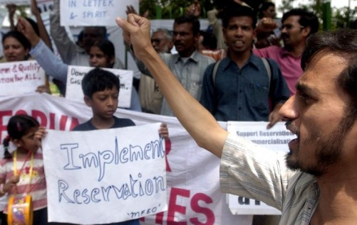 """Pro-reservation activists hold placards and shout slogans as they demand the immediate implementation of the 27 percent quota for backward classes announced by the Indian government in New Delhi, 05 June 2006. Resident doctors in India's capital bowed to a Supreme Court directive and ended a 20-day strike against higher college quotas for disadvantaged students """"in the interest of patient care"""". / AFP / MANPREET ROMANA"""