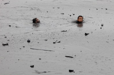 An oil firefighter worker is rescued after been submerged underneath the thick oil slick. The worker ran into trouble as he was attempting to fix an underwater pump during oil spill cleanup operations in Dalian, China. The spill was caused by a pipeline blast at the Dalian Port, causing severe threats to coastal waters, ecosystems and marine life with significant consequences to the fishing industry, tourism and local communities.