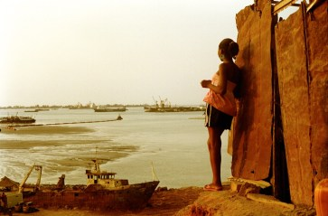 In the bay of Luanda,cargo ships wait interminally to offload their merchandise in the chaotic port surrounded by slums populated by people exiled by 27 years of civil war. After 30 years of civil war, Angola is a ruined country.Landmines litter the countryside, 47% of the population is aged 14 or under and women outnumber male survivors of the war by 10 to 1. To rebuild the country the simplicity of the loop is implacable: Beijing lends money to Angola which in turn hires chinese companies, while in passing skimming money off the top. In exchange Angola promises China 30 % of its crude oil. Since 2007, Angola has edged out Saudi Arabia as the leading provider of crude oil to China while 70 % of its population lives below the poverty line.