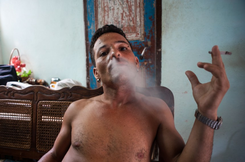 a man smoking with friends in his one room home in Old Havana