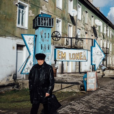 A woman walks past the sign showing the way to the Lonea Mine, in Lonea, Romania.