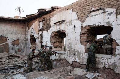 Syriac army members take position in a church destroyed by fighters of Islamic State