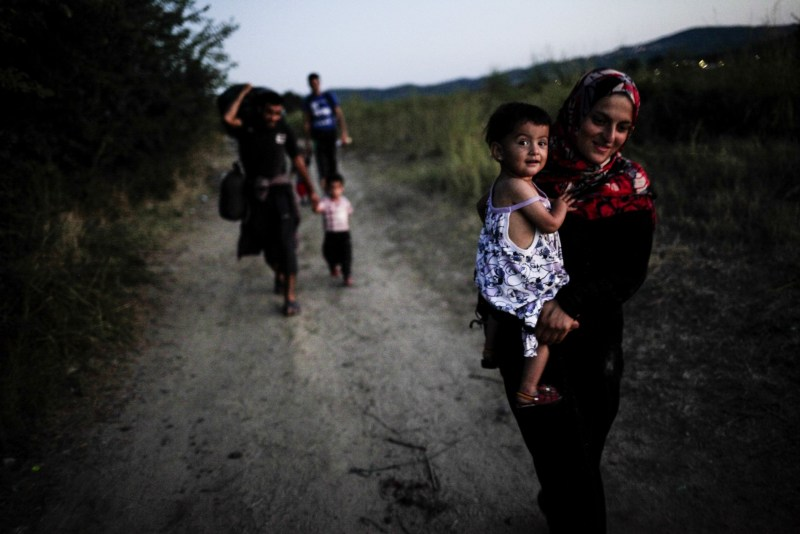 Refugees after crossing the Greek-Macedonian border walk towards the train that will take them to the Macedonian-Serbian border. Gevgelija, August 23, 2015.