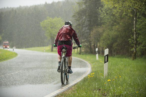 Mann fährt auf dem Fahrrad im strömenden Regen einen Anstieg hinauf
