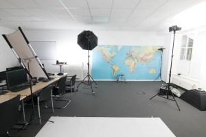 Blick in einen Raum mit Foto-Ausrüstung vom mobilen Studio mit Hohlkehle, Studioblitzen und Reflektor