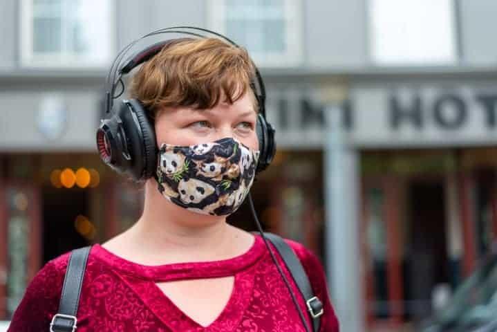 Meisje met mondkap en koptelefoon wacht op de bus - Straatfotografie Groningen