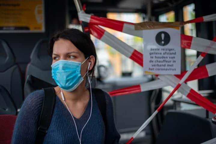 Meisje met mondkapje op in de bus