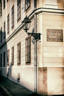 """Vintage style photo of an old lantern at the corner of the street. The street sign in old croatian and german laguages reads """"Gentlemans' Street""""."""