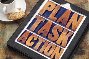 plan, task, action word abstract - text in vintage letterpress wood type on a digital tablet with a cup of coffee, management concept